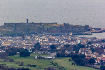 Looking at Peel Castle over part of Peel and the Golf Course Club House from the Cairn, by Paul Smith