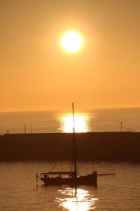 Sailing boat sunset and breakwater, by Dave Corkish